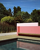 Corner detail of a modern pink-painted wall with a wooden bench in front of a pool