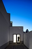 A roof terrace with an illuminated entrance in the evening