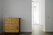 A simple wooden chest of drawers against a white wall and an open doorway with a view of a glass door