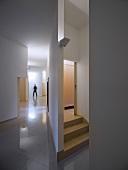 Puristischer Vorraum mit hochglänzendem Fliesenboden und Blick auf Treppenaufgang hinter Trennwand