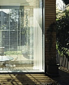 A corner of a house with blinds at the floor-to-ceiling windows