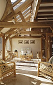 A country house with wooden beams and a wicker furniture in the living room