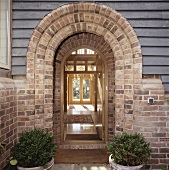 A glazed front door with a brick arch and a view into the hallway