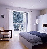 A modern bedroom with a double bed and an armchair next to an open balcony door
