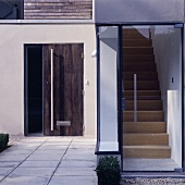 A glazed entrance to a modern house with a view of the stairs and an additional wooden front door