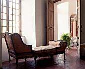 Zierliche, antike Chaiselongue auf wabenförmigen Terracottafliesen in historischem, französischem Altbau