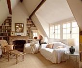 Sitzgruppe mit weissen Überwürfen und Rattan-Liegestuhl vor Kamin mit Bücherregal in naturfarbenem Wohnzimmer mit Spitzdach