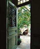 Blick durch grüne, alte Tür mit geschwungenem Schmiedeeisengitter in Wintergarten mit Palme