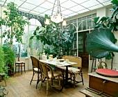 Antike Korbmöbel, Leuchter und Grammophon in Wintergarten-Esszimmer mit Holzboden und flachem Glasdach