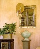 Antiker Spiegel mit Strohhut über Urne auf Sockel vor apricotfarbiger Wand