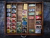 Sammlung alter Dosen mit Grammophon-Nadeln in Holzschublade