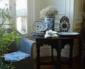 Englischer, blauer Korbsessel neben antikem Tisch mit blau-weißem, chinesischem Porzellan und Uhr in traditionellem Wohnzimmer
