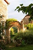 Mauerruine mit Torbogen in historischem Gebäudeensemble in der Landschaft