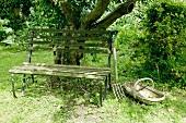 Alte Gartenbank, Grabgabel und Obstkorb unter Baum in wildem, ländlichem Garten