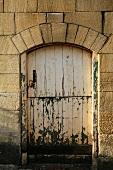 Abgeblätterte Farbe an alter Stalltür mit bogenförmigem Sturz in historischer Natursteinfassade