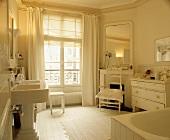 Weisses Wohnbad mit antiken Möbeln, Säulenwaschbecken und grossem Spiegel über Kamin