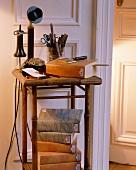 30er-Jahre-Telefon und Stapel Bücher mit marmoriertem Einband auf altem Bambustisch