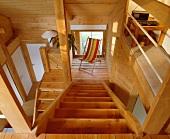Blick auf Treppenpodest mit gestreiftem Liegestuhl in offenem, holzverkleidetem Wohnraum