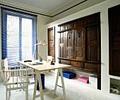 Blaue Jalousie, Regiestuhl und Schreibtischplatte im Kontrast zu Einbauschränken mit antiken, geschnitzten Holztüren
