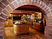 Blick durch rustikales Backsteingewölbe auf moderne Küche aus Holz mit ovaler Kochinsel und Steinboden