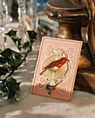 Gemaltes Rotkehlchen auf altmodischer Weihnachtskarte als Teil einer Tischdekoration