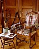 Tweedweste auf kariert gepolstertem Holzstuhl mit passendem Tischchen vor Angel-Equipement in englischem Landhaus