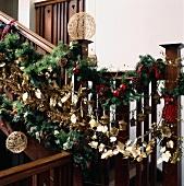 Üppige, englische Weihnachtsgirlande aus Tannenzweigen, Goldblättern und roten Kugeln an hölzernem Treppengeländer