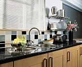 Rundes Edelstahlbecken mit Abtropfschale in Granitarbeitsfläche unter geschlossener Metalljalousie in moderner Küche