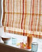 Naturfarben gestreifte Jalousie über Fensterbank mit farblich passenden Dekoartikeln und hellblauen Glasbechern