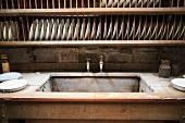 Langes Tellergestell aus Holz über rustikaler, alter Holzspüle