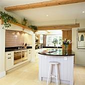 Cremefarbene Einbauküche mit holzfarbenen Elementen, weisser Kochinsel und Kalksteinboden