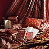 Alte Bücher mit marmoriertem Einband dekorativ drapiert auf rot/rosé und gold gemusterten Kissen und Vorhangstoffen