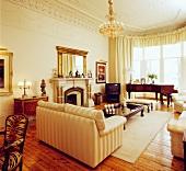 Elfenbeinfarbenes Interieur, Kronleuchter und Stuckdecken im Kontrast zu Kieferndielenboden in traditionellem Wohnzimmer