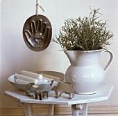 Hand-aufs-Herz-Backform an Wand hinter weißem Holztischchen mit Krug, Teller mit Kerzen und Ausstechformen