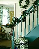 Türkisblaues, traditionelles Treppengeländer mit weihnachtlicher Efeugirlande und Geschenken neben Blick in Esszimmer