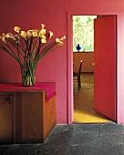 Vase mit Callas auf hölzernem Schrank in einem mexikanischen Saal mit leuchtend rosa Wänden und grauem Steinboden