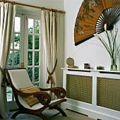 Armlehnstuhl (Planter's Chair) im Landhausstil vor Terrassentür und Wanddekoration mit großem Fächer über verkleidetem Heizkörper