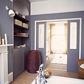 Ein Badezimmer mit grauen Einheiten und Schiebetüren zum Schlafzimmer