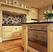 Cremefarbener Aga und ein moderner Elektro-Backofen in einer Küche
