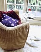 Ein Korbsessel mit lila Kissen und ein Beistelltisch vor dem Fenster