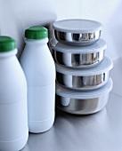 weiße Kunststoff-Flaschen neben Edelstahl-Aufbewahrungsboxen