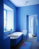 Frei stehende Badewanne vor dem Fenster in einem Badezimmer mit blauen Wänden