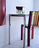 Bunt gestreifter Stuhl aus Plexiglas und ein Metalltisch