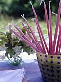 Lange rosa Kerzen in einem Topf auf dem Tisch