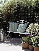weiße Metallbank auf Terrasse mit blühenden Pflanzen in Töpfen