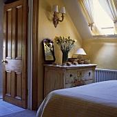 Weissliche antike Holzkommode unter Dachflächenfenster in gelb-weißem Schlafzimmer mit offener Tür zum Badezimmer ensuite