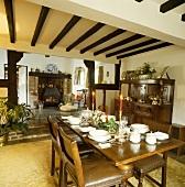 Schwarzes Holz in Kontrast zu weißem Mauerwerk in offenem Wohn-Essbereich mit festlich gedecktem Tisch und Kamin