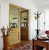 Halb verglaste Doppeltür zwischen Wohnzimmer und Eingangsbereich mit Bugholz-Garderobenständer und bemaltem Spazierstockhalter