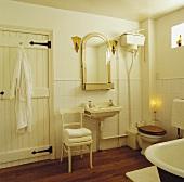 Cremefarbenes antikes Badezimmer mit honigfarbenen Lämpchen als Spiegelbeleuchtung und brennender Kerze neben WC