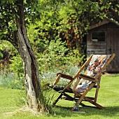 Holzliegestuhl mit blumig gemustertem Stoffbezug unter Baum in einem Sommergarten